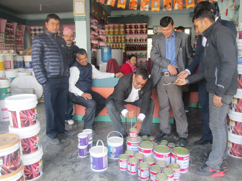 One of the members of the Kaski District Market Monitoring Committee destroys expired paints in Pokhara, on Tuesday, February 7, 2017. Photo: Rishi Ram Baral