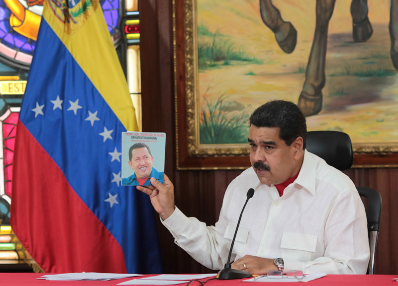 Venezuela's President Nicolas Maduro holds an image of Venezuela's late President Hugo Chavez as he speaks during a meeting with governors in Caracas, Venezuela on February 14, 2017. Photo: Miraflores Palace via Reuters