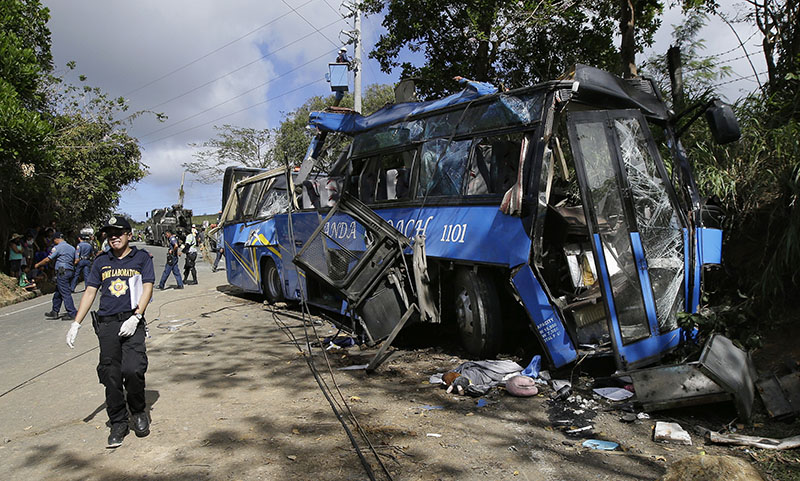 A police investigator passes by the wreckage of a bus that crashed on a downhill road in Tanay, Rizal province, east of Manila, Philippines, on Monday, February 20, 2017. Photo: AP