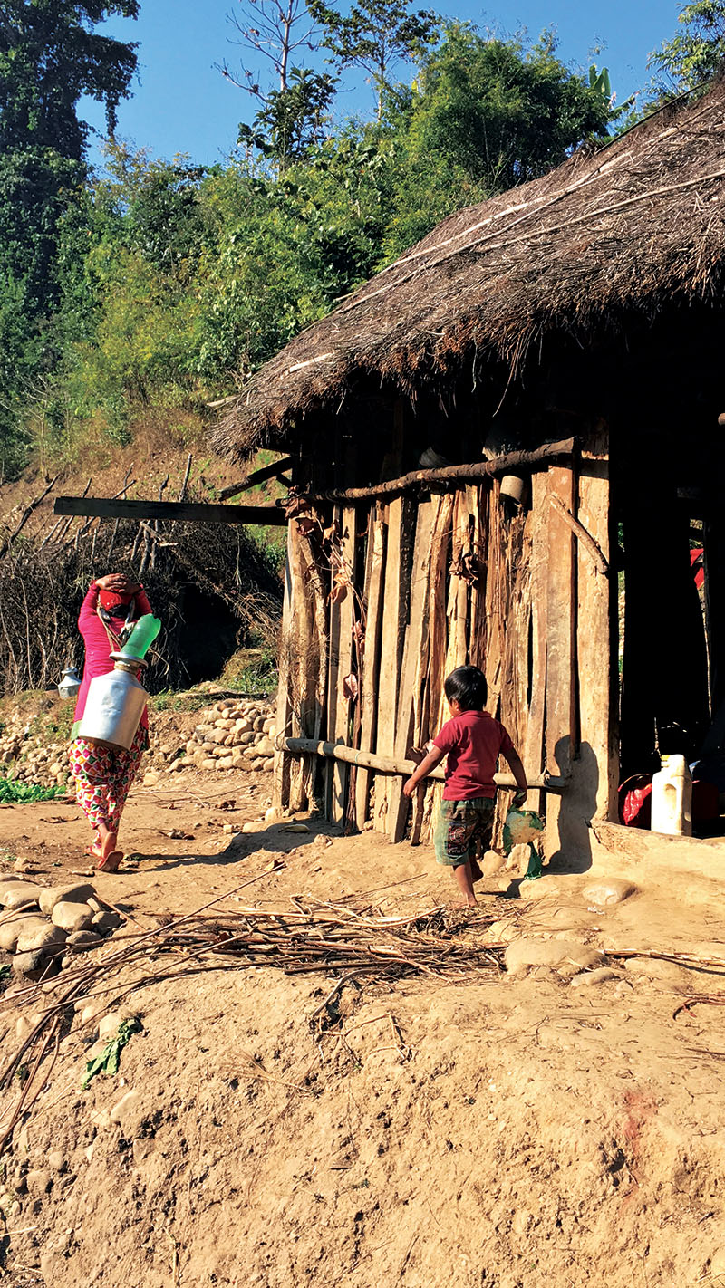 A child running after his mother as she fetches drinking water outside their makeshift shelter, in Hadikhola village, Makawanpur.