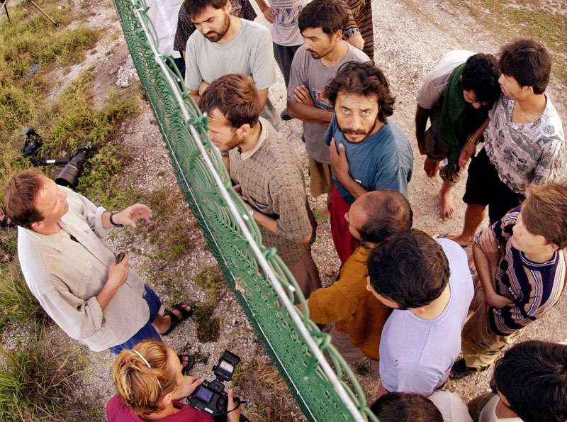 File - Refugees (right) gather on one side of a fence to talk with international journalists about their journey that brought them to the Island of Nauru, on September 19, 2001. Photo: AP