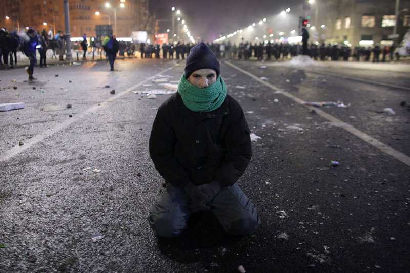 A protestor sits on the ground following scuffles between protestors and Romanian police at a demonstration in Bucharest, Romania, on February 1, 2017. Photo: Inquam Photos via Reuters