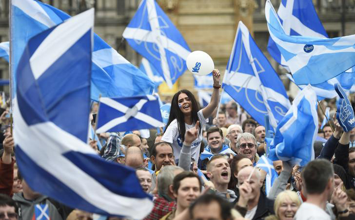 Campaigners wave Scottish Saltires at a 'Yes' campaign rally in Glasgow, Scotland September 17, 2014. The referendum on Scottish independence will take place on September 18, when Scotland will vote whether or not to end the 307-year-old union with the rest of the United Kingdom.      REUTERS/Dylan Martinez (BRITAIN  - Tags: POLITICS ELECTIONS)
