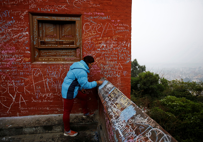 A woman writes with chalk on a wall.