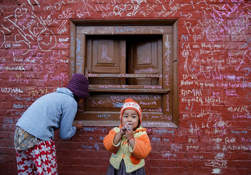 A girl (left) writes on a wall of Saraswati temple.