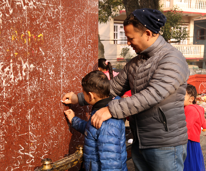 A father helps his child write with chalk on a wall.