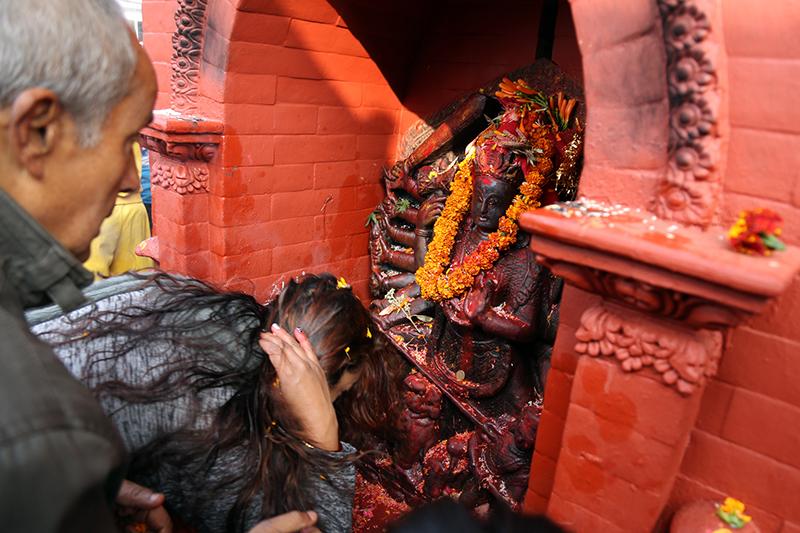 Devotees worship an idol of Saraswati.