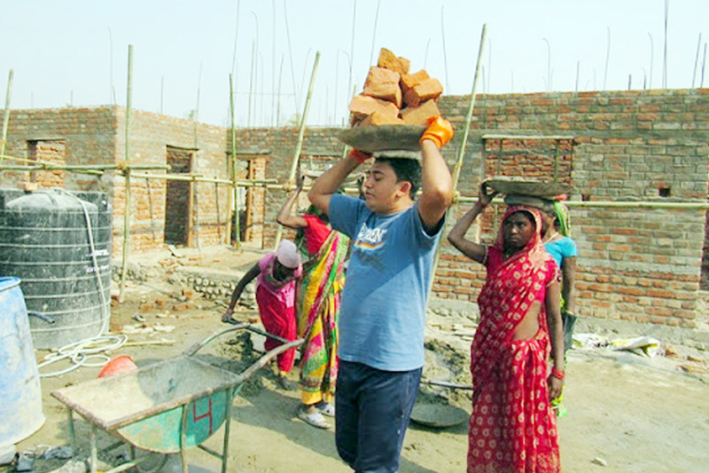 Nepal's comedian artist Sitaram Kattel carries bricks on his head during the on-going construction of an integrated Musahar settlement in Mohattari district, on Thursday, February 16, 2017. Photo: RSS