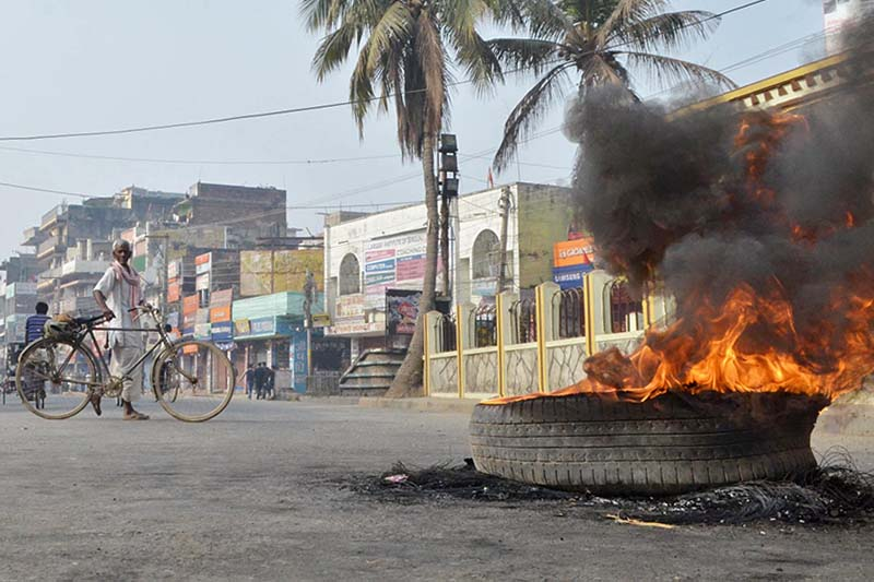 A man passes by a burning tyre in Ghantaghar Chok of Birgunj on Wednesday, February 22, 2017. Cadres of the United Democratic Madhesi Front have staged demonstration in various parts of the city protesting the governmentu2019s announcement of the poll dates. Photo: Ram Sarraf/THT