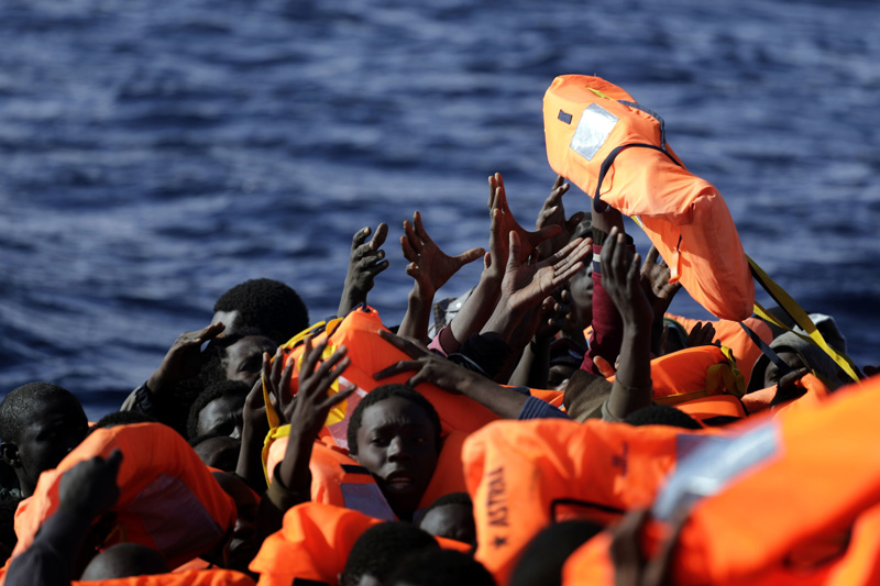 FILE - In this Jan. 27, 2017 file photo, sub-Saharan migrants raise their hands to grab a life jacket as they are rescued by members of the Proactive Open Arms NGO, in the Mediterranean Sea north of Zumarah, Libya. Photo: AP