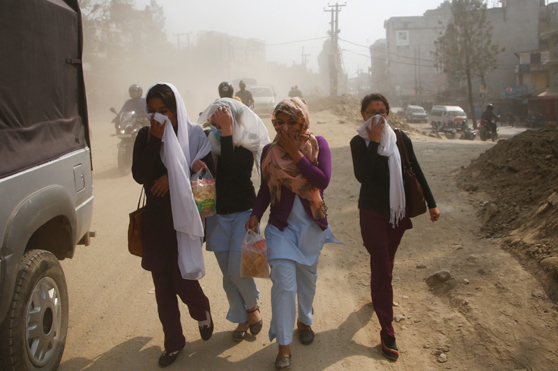 Pedestrians cover their face as they walk along the dusty road in Kathmandu, Nepal February 27, 2017. Photo: Reuters