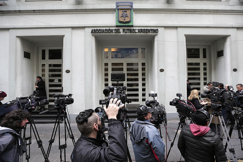 FILE - journalists stand outside the headquarters of the Argentine Football Association, AFA, in Buenos Aires, Argentina, on May 31, 2016. Photo: AP
