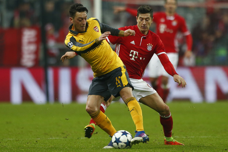 Arsenal's Mesut Ozil in action with Bayern Munich's Robert Lewandowski. Photo: Reuters