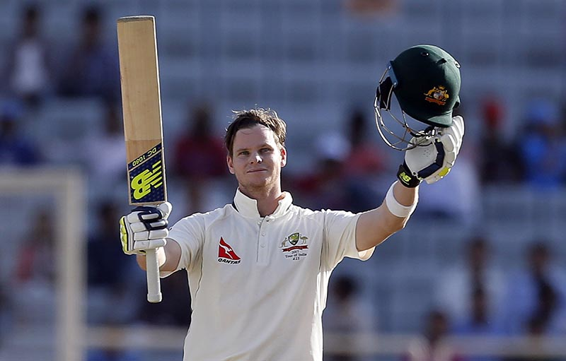 Australia's captain Steven Smith raises his bat and helmet to celebrate scoring a century during the first day of their third test cricket match against India in Ranchi, India, Thursday, March 16, 2017. Photo: AP