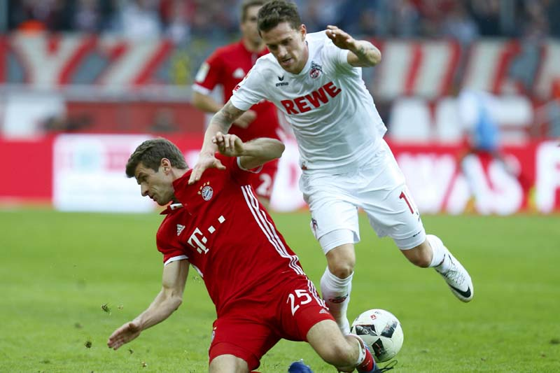 FC Cologne's Simon Zoller tackles Thomas Mueller of Bayern Munich. Photo: Reuters