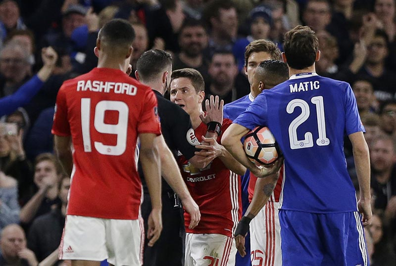 Manchester United's Ander Herrera, centre, argues with referee Michael Oliver (second left) after he was given a red card and sent him off during the English FA Cup quarterfinal soccer match between Chelsea and Manchester United at Stamford Bridge stadium in London, on Monday, March 13, 2017. Photo: AP