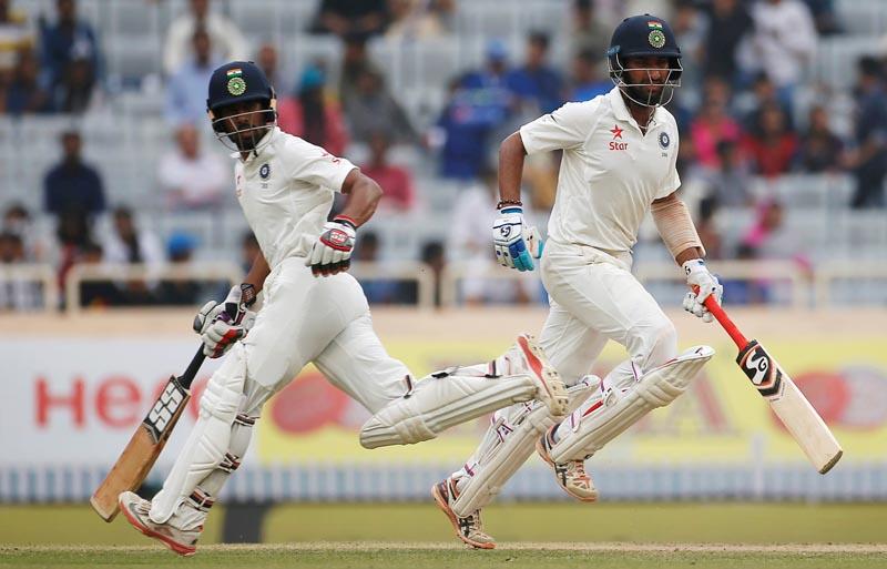 India's Cheteshwar Pujara (R) and Wriddhiman Saha run between the wickets. Photo: Reuters