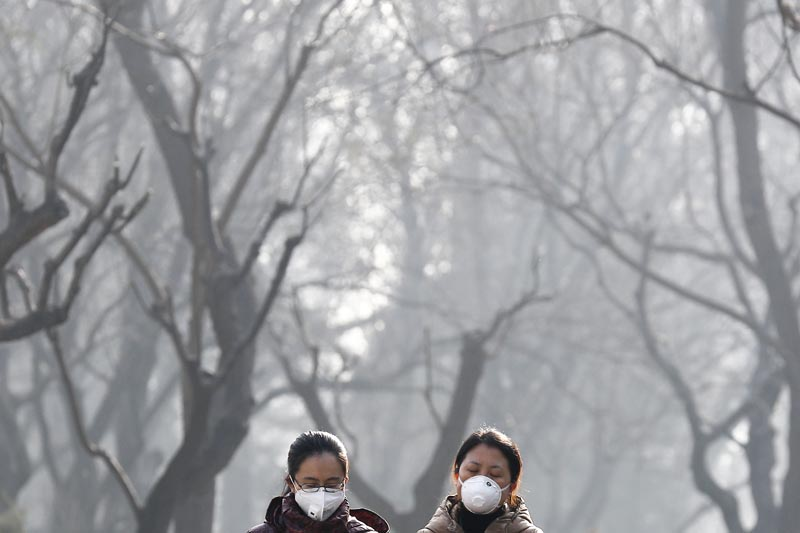FILE - on December 19, 2016, file photo, Chinese women wearing masks to protect themselves from air pollution walk through Ritan Park shrouded by dense smog in Beijing. China's government said on Wednesday, March 29, 2017, it will stick to its promises to curb carbon emissions after President Donald Trump eased US rules on fossil fuel use that were meant to control global warming. A Chinese foreign ministry spokesman said Beijing is committed to the Paris climate agreement. Photo: AP