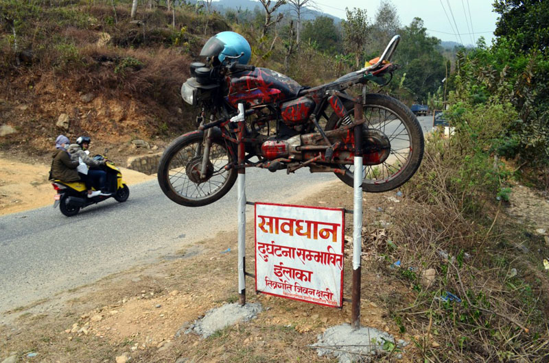 A damaged motorcycle is mounted as a warning to make people aware about possible accidents along the Malekhu-Dhading Besi road section in Dhading district on Wednesday, March 1, 2017. Photo: Keshav Adhikari