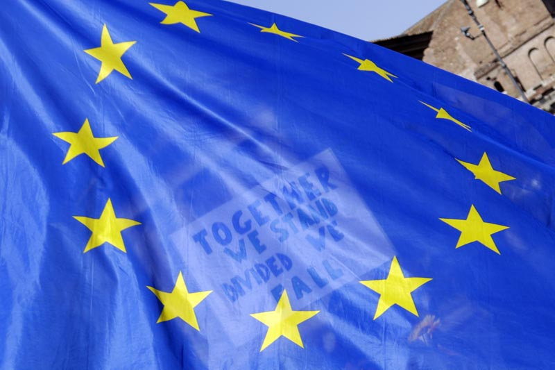 A placard in support of the European Union is seen through an European flag as demonstrators prepare to take part into a demonstration in support of the European Union in Rome, Saturday, March 25, 2017, the day leaders of the European Union gathered in Rome to mark the 60th anniversary of the bloc. Photo: AP
