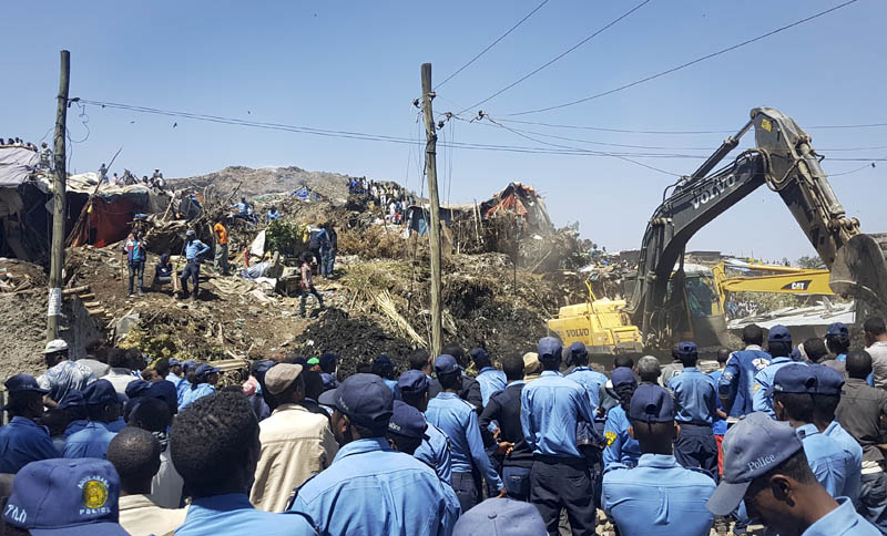 Police officers secure the perimeter at the scene of a garbage landslide, as excavators aid rescue efforts, on the outskirts of the capital Addis Ababa, Ethiopia Sunday, March 12, 2017. Photo: AP