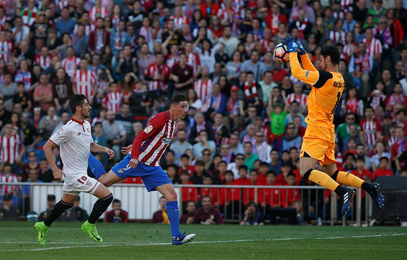 Sevilla's goalkeeper Sergio Rico stops Atletico Madrid's Fernando Torres' shot. Photo: Reuters