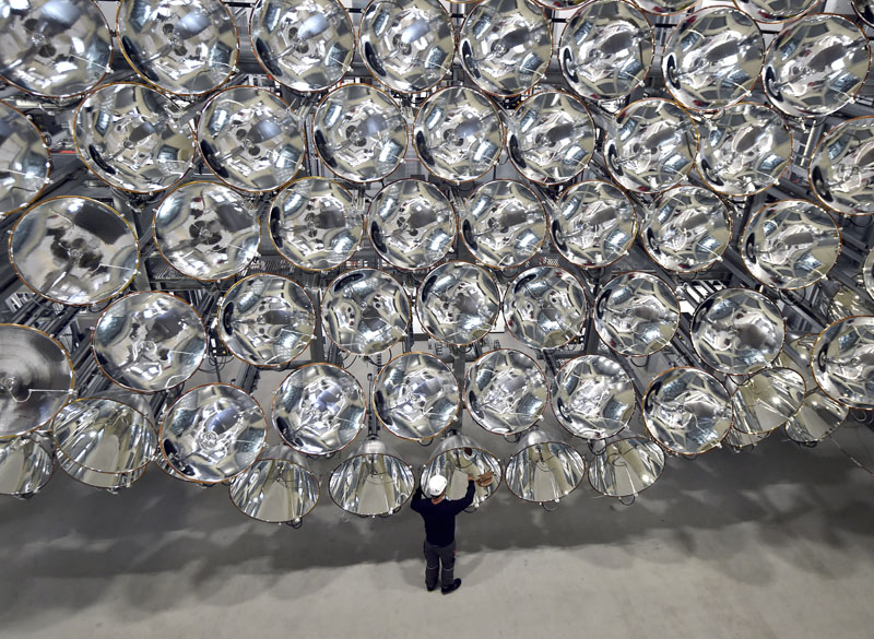 In this March 21, 2017 photo engineer Volkmar Dohmen stands in front of xenon short-arc lamps in the DLR German national aeronautics and space research center in Juelich, western Germany. The lights are part of an artificial sun that will be used for research purposes.  (Caroline Seidel/dpa via AP)