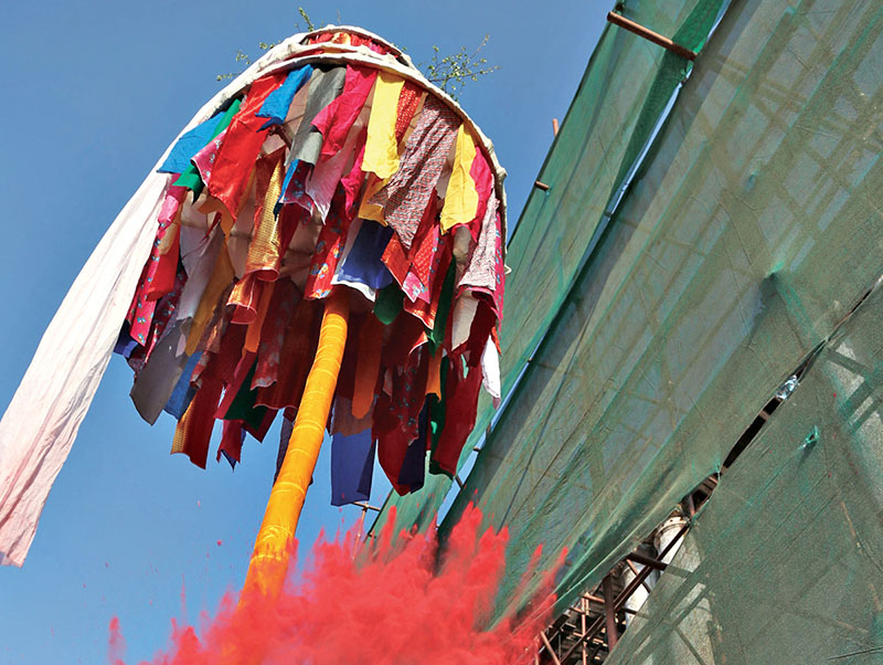 FILE - A man throws vermilion powder after erecting chir, a wooden pole, to mark the beginning of Holi festival, in Basantapur, Kathmandu, on Sunday, March 6, 2017. Photo: RSS