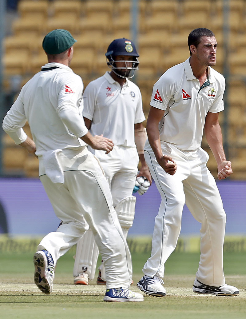 Australia's Mitchell Starc (right) celebrates the dismissal of India's Karun Nair during the fourth day of their second test cricket match in Bangalore, India, on Tuesday, March 7, 2017. Photo: AP