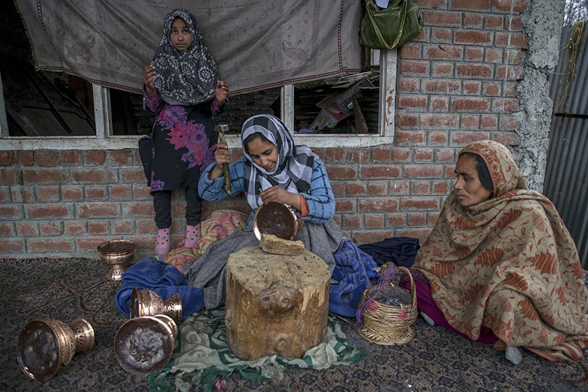 In this March 9, 2017 photo, Beenish, daughter of former Kashmiri militant Syed Bashir Bukhari who committed suicide, engraves motifs on copper vessel as her mother Safeena Bashir, right, and her sister Bismah watch her at their residence in Kreeri, 35 km north of Srinagar Photo: AP Photo