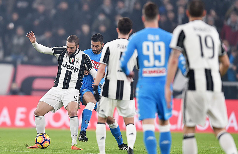 Juventus' Gonzalo Higuain (left) and Napoli's Raul Albiol vie for the ball during the Italian Cup first leg semifinal soccer match between Juventus and Napoli, at the Juventus Stadium in Turin, Italy, on Tuesday, February 28, 2017. Photo: Andrea Di Marco/ANSA via AP