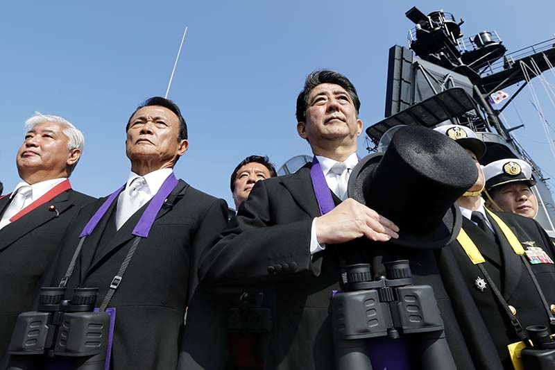 File-Japanese Prime Minister Shinzo Abe (centre), stands with Deputy Prime Minister and Finance Minister Taro Aso (second from left) and then Defense Minister Gen Nakatani (left) during the official triennial Maritime Self-Defense Force fleet review aboard the JMSDF escort ship Kurama in the waters off Sagami Bay, south of Tokyo, Japan on October 18, 2015. Photo: Kyodo News via AP