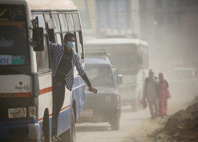 A bus conductor wearing a mask hangs onto a bus as he travels through a dusty road in Kathmandu, Nepal February 27, 2017. Photo: Reuters