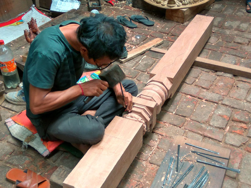 An artist carves on a wooden column for the reconstruction of Lunchhen Nani Phalcha, destroyed by the Gorkha Earthquake 2015, in Chabahal, Tangal of Patan in 2016. Photo Courtesy: SAI Help Nepal