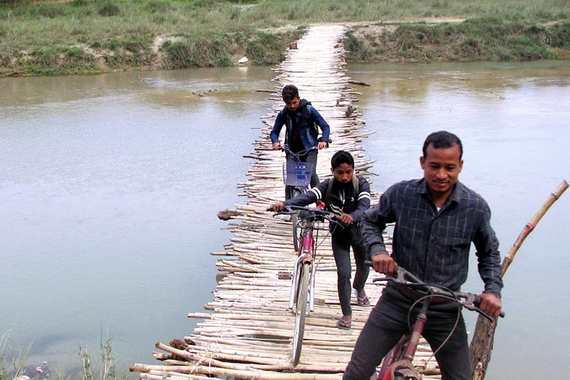 Locals use a makeshift bridge to cross the Mohana River in Kanchanpur district, on Monday, March 20, 2017. Photo: RSS