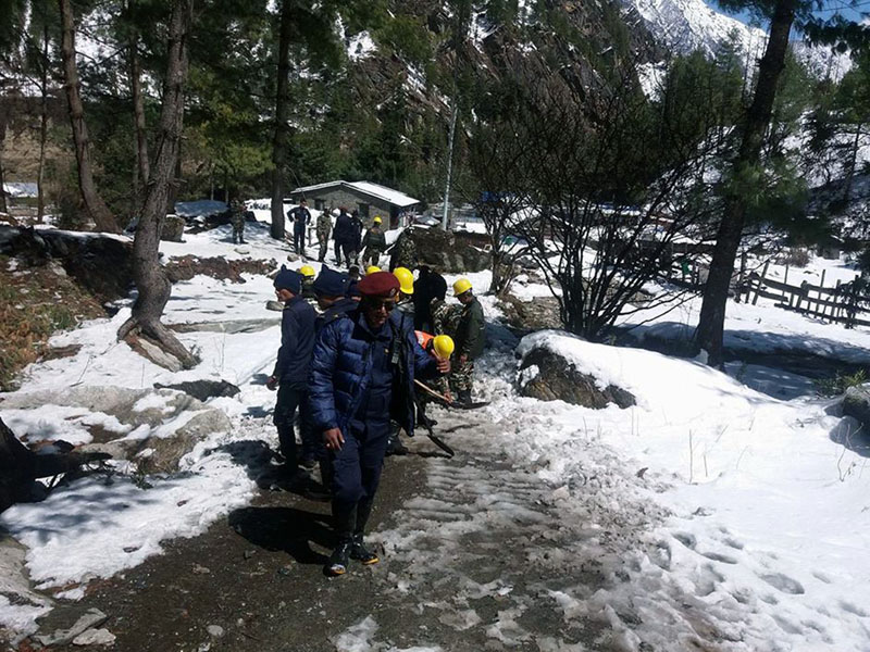 A joint team of security personnel from Nepal Police and Nepal Army shovel the driveway, in Chame, Manang district, on Tuesday, March 14, 2017. Photo: RSS