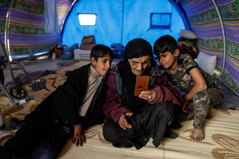Khatla Ali Abdullah (90) who recently fled her house in Al Mamoun district looks at photographs on a mobile phone as she sits with her grandsons in her tent in Hammam al Alil camp while Iraqi forces battle with Islamic State militants, in western Mosul, Iraq, on  March 1, 2017. Photo: Reuters