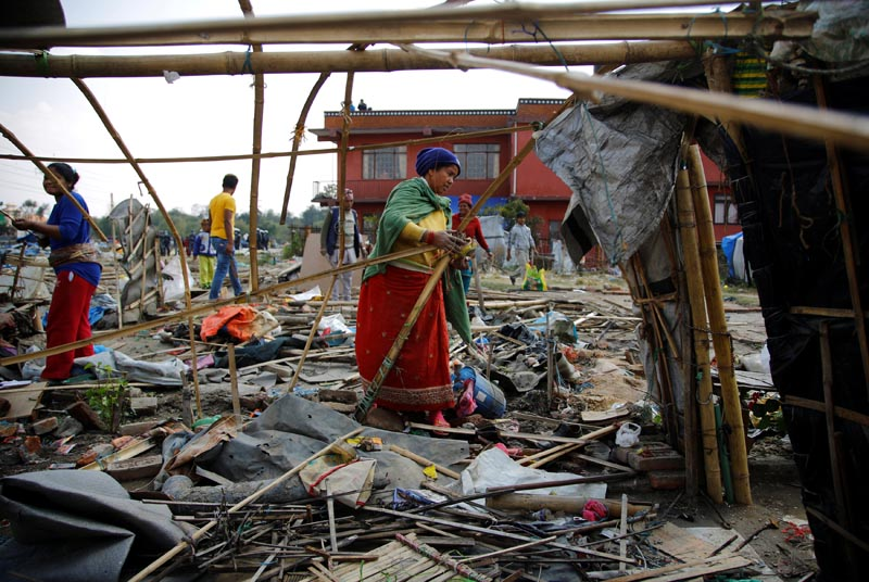 People scavenge for their belongings after the makeshift shelters were demolished at the displacement camp for earthquake victims at Chuchepati in Kathmandu, Nepal, on March 14, 2017. Photo: Reuters