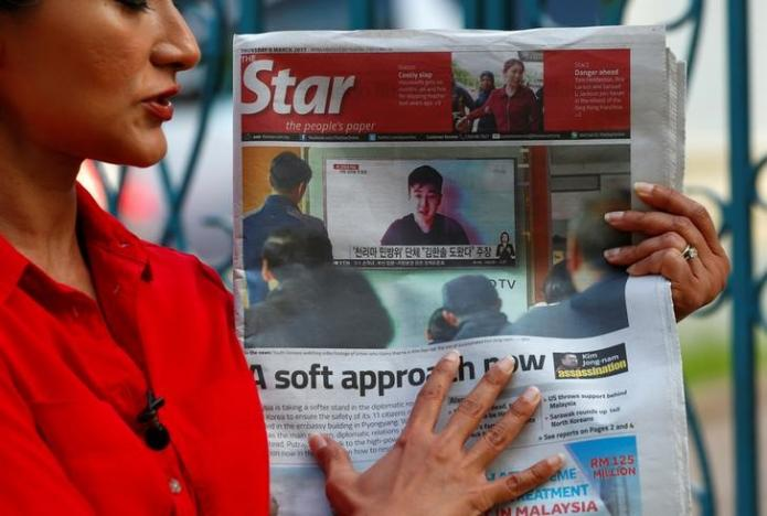A journalist holds up a newspaper showing a photo of a man who claims to be the son of Kim Jong Nam outside the North Korean embassy in Kuala Lumpur, Malaysia March 9, 2017. REUTERS/Edgar Su/Files