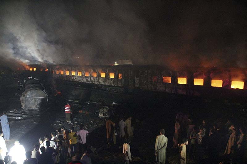 People look at a burning passenger train in Shaikhupura, near Lahore, Pakistan, on Tuesday, March 28, 2017. Photo: AP