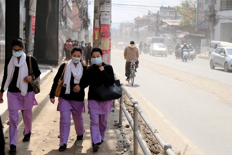 Padestrians put on mask to sheild from dust pollution caused by the installation of Melamchi Drinking Water Project in kathmandu, on Tuesday, March 14, 2017. Photo: RSS