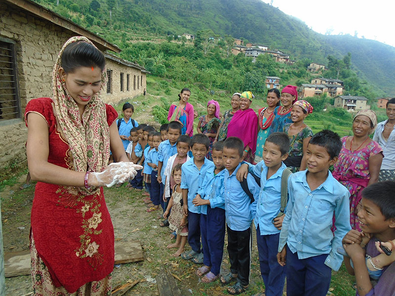 A woman showing children and their guardians how to wash hands, in Jhula VDC, Rukum, on Monday, March 13, 2017. Photo: THT
