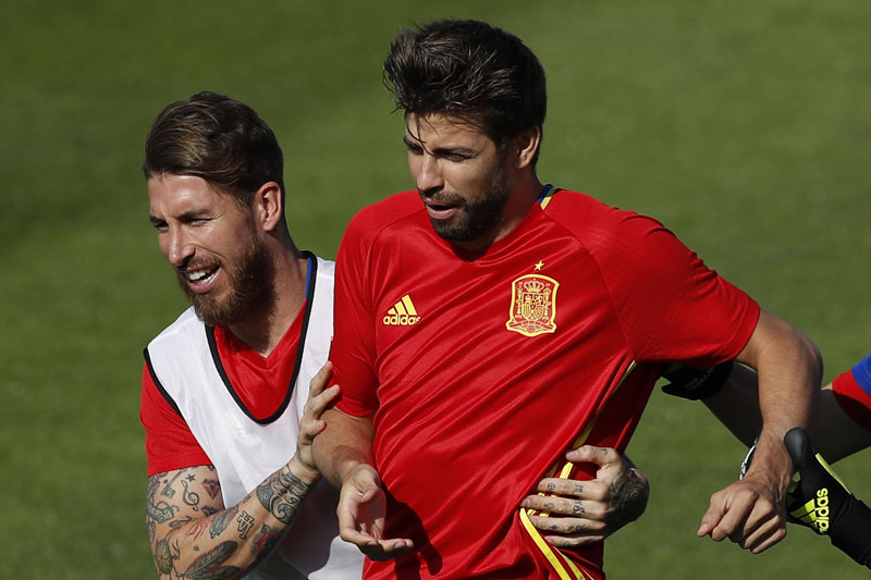 FILE - Spain's Sergio Ramos (left) grabs Gerard Pique during a training session at the Sports Complex Marcel Gaillard in Saint Martin de Re in France, on June 24, 2016. Photo: AP