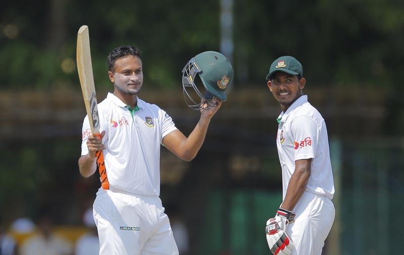 Bangladeshi batsman Shakib Al Hasan, left, celebrates scoring a century as teammate Mosaddek Hossain watches on day three of their second test cricket match in Colombo, Sri Lanka, Friday, March 17, 2017. Photo: AP