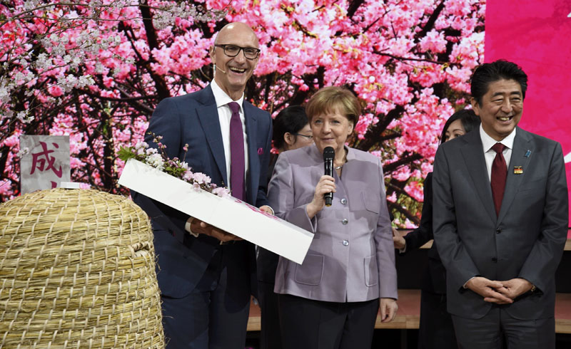 Japanese Prime Minister Shinzo Abe and German Chancellor Angela Merkel at the Deutsche Telekom booth with CEO Timotheus Hoettges during a media tour of the world's biggest computer and software fair, CeBit, in Hanover, Germany, March 20, 2017. Photo: Reuters
