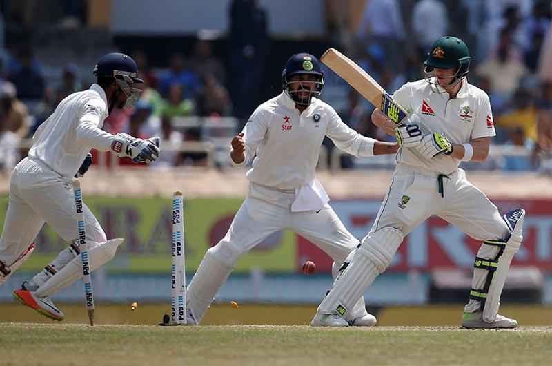 Australia's captain Steven Smith (R) is clean bowled. Photo: Reuters