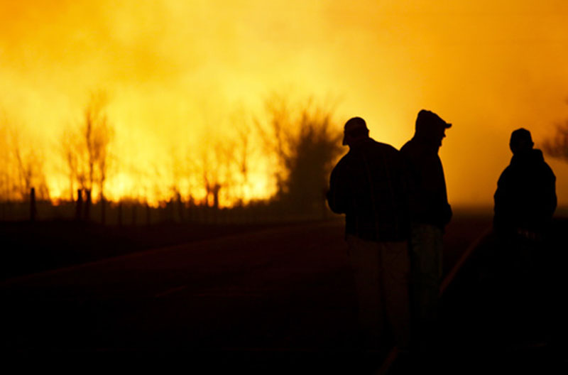 People are silhouetted against the orange glow of the fire as they watch a large grass fire burning out of control, on Monday, March 6, 2017, in the northeast of Hutchinson, Kansas. Photo: Lindsey Bauman/The Hutchinson News via AP