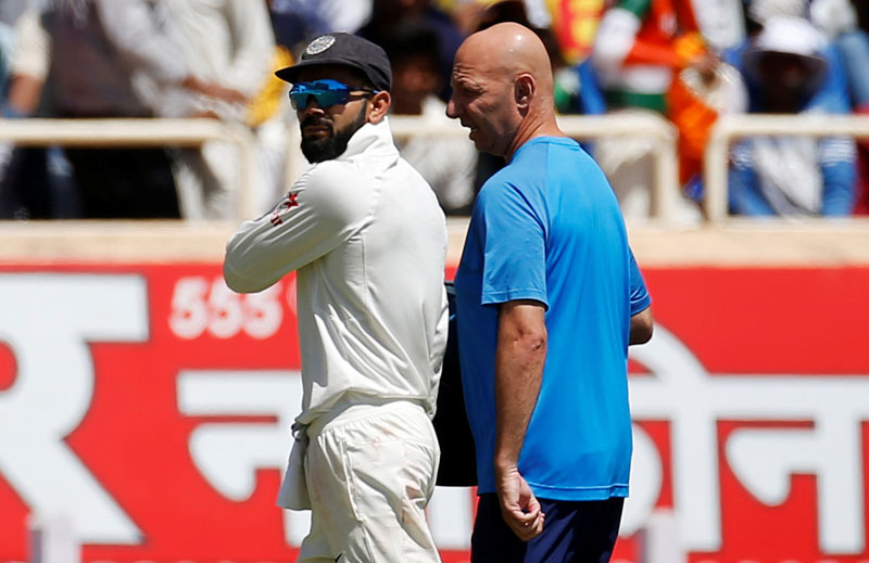 India's captain Virat Kohli (L) walks off the field after injuring himself. Photo: Reuters