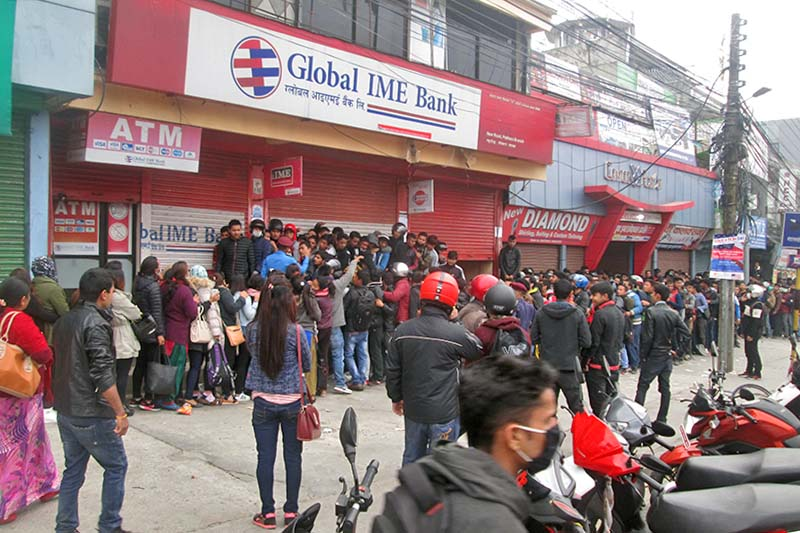 Youth line up outside the Global IME Bank Limited to fill the Korean Language Test forms online in New Road of Pokhara on Wednesday, March 22, 2017. Police personnel were deployed in order to control the mob. Photo: Rishi Ram Baral