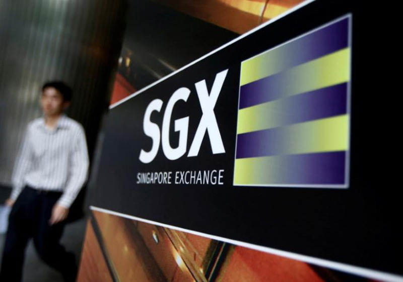 An office worker walks past a logo of the Singapore Stock Exchange (SGX) outside its premises in Singapore, on  April 23, 2014. Photo: Reuters